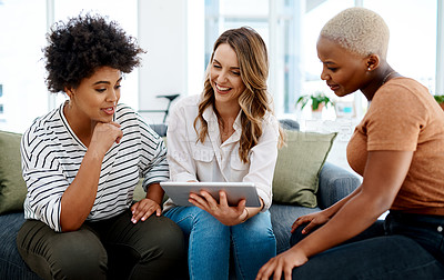 Buy stock photo Shot of a group of businesswomen working together on a digital tablet in an office