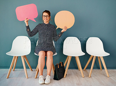 Buy stock photo Studio portrait of an attractive young businesswoman holding up speech bubbles while sitting in line against a grey background