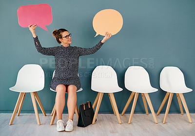 Buy stock photo Studio shot of an attractive young businesswoman holding up speech bubbles while sitting in line against a grey background
