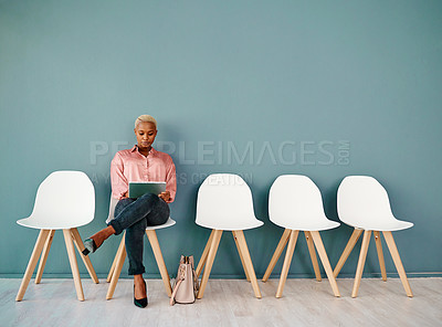 Buy stock photo Studio shot of an attractive young businesswoman using a digital tablet while sitting in line against a grey background