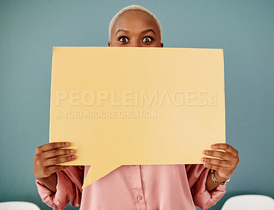 Buy stock photo Studio portrait of an attractive young businesswoman covering her face with a speech bubble while sitting in line against a grey background