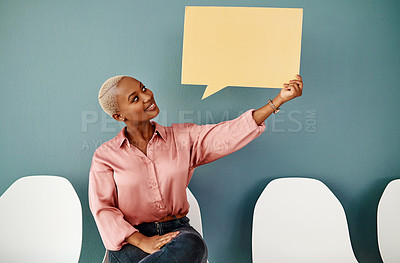 Buy stock photo Studio shot of an attractive young businesswoman holding up a speech bubble while siting in line against a grey background