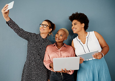 Buy stock photo Studio shot of a group of attractive young businesswomen taking a selfie together while standing against a grey background