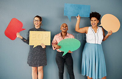 Buy stock photo Studio portrait of a group of attractive young businesswomen holding speech bubbles while standing against a grey background