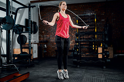 Buy stock photo Full length shot of an attractive young female athlete skipping in the gym