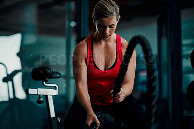 Buy stock photo Cropped shot of an attractive young female athlete working out with battle ropes in the gym