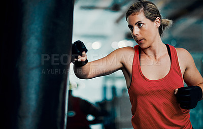Buy stock photo Cropped shot of an attractive young female kickboxer working out in the gym