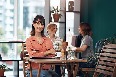 Buy stock photo Portrait of an attractive middle aged woman having coffee by herself at a coffee shop during the day