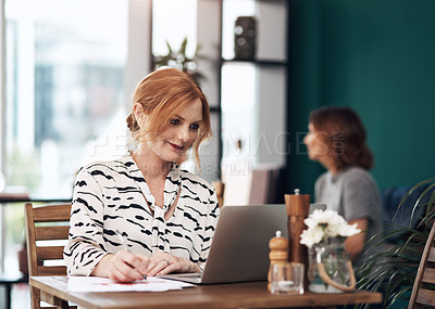 Buy stock photo Cropped shot of an attractive middle aged woman working on her laptop while making notes inside of a coffee shop during the day