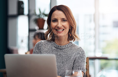 Buy stock photo Portrait of an attractive middle aged woman working on her laptop while being seated inside of a coffee shop during the day