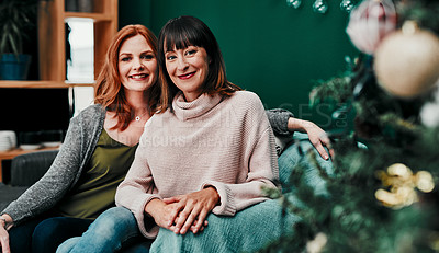 Buy stock photo Portrait of two attractive middle aged women sitting together on a sofa next to a Christmas tree at home