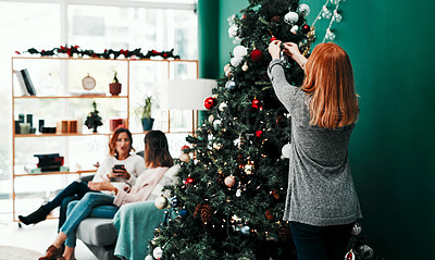 Buy stock photo Rearview shot of an unrecognisable woman decorating a Christmas tree at home during the day