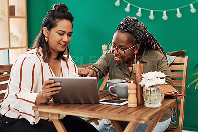 Buy stock photo Shot of two young women using a digital tablet together at a cafe