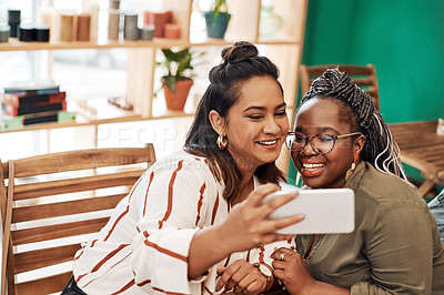 Buy stock photo Shot of two young women taking selfies at cafe