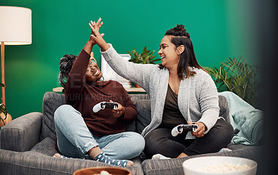 Buy stock photo Shot of two young women giving each other a high five while playing video games on the sofa at home