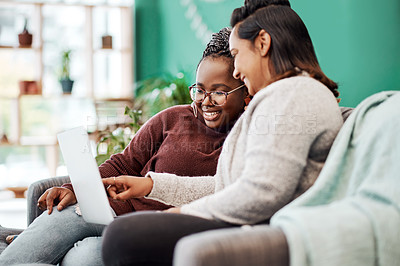 Buy stock photo Shot of two young women using a laptop on the sofa at home