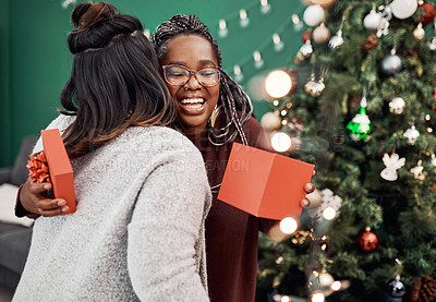 Buy stock photo Shot of two happy young women exchanging gifts during Christmas at home