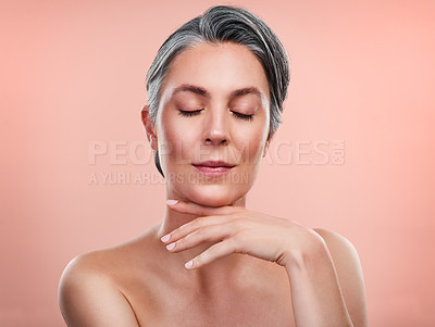 Buy stock photo Studio shot of a beautiful mature woman posing against a peach background