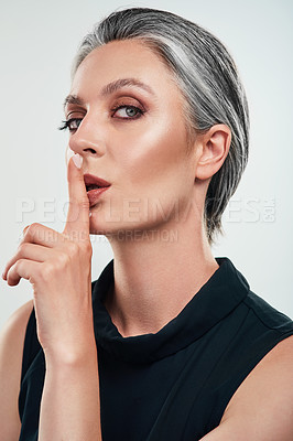Buy stock photo Studio portrait of a beautiful mature woman posing with her finger on her lips against a grey background