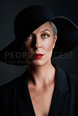 Buy stock photo Studio portrait of a beautiful mature woman wearing a hat and posing against a dark background