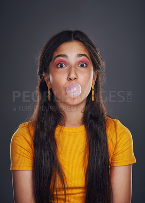 Buy stock photo Cropped portrait of an attractive teenage girl standing against a dark background alone and blowing bubbles with bubblegum