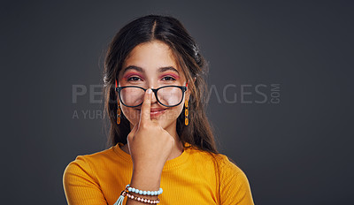 Buy stock photo Cropped portrait of an attractive teenage girl wearing glasses and standing against a dark background in the studio alone