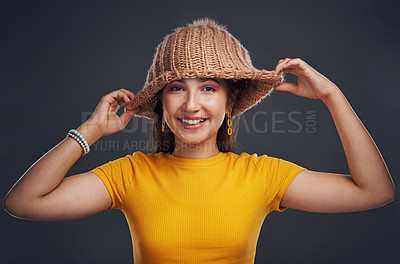 Buy stock photo Cropped portrait of an attractive teenage girl wearing a beanie and feeling playful against a dark studio background