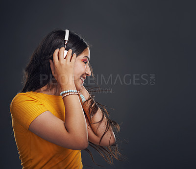 Buy stock photo Cropped shot of an attractive teenage girl standing against a dark background alone and listening to music through headphones