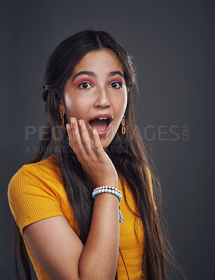 Buy stock photo Cropped portrait of an attractive teenage girl standing alone and looking surprised against a dark background in the studio