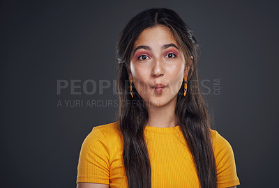 Buy stock photo Cropped portrait of an attractive teenage girl standing alone and feeling playful against a dark background in the studio