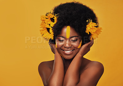 Buy stock photo Studio shot of a beautiful young woman smiling while posing with sunflowers in her hair against a mustard background