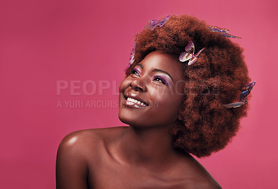 Buy stock photo Studio shot of a beautiful young woman smiling while posing with butterflies in her hair against a purple background