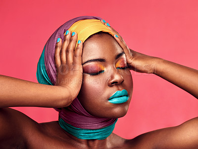 Buy stock photo Studio shot of a beautiful young woman wearing a head wrap and make up against a pink background