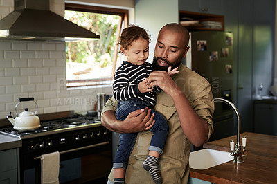Buy stock photo Shot of a young man spending quality time with his adorable child at home