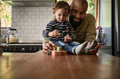 Buy stock photo Shot of a young man and his adorable child playing with building blocks together at home