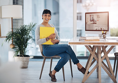Buy stock photo Full length portrait of an attractive young businesswoman sitting alone and holding files in her office