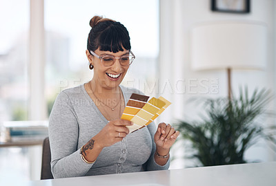Buy stock photo Cropped shot of an attractive young businesswoman sitting alone in her office and looking at a colour swatch