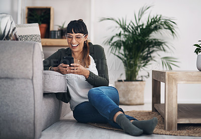 Buy stock photo Full length shot of an attractive young woman sitting in her living room alone and using her cellphone