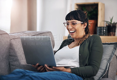Buy stock photo Cropped shot of an attractive young woman sitting alone in her living room and using her laptop