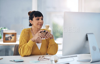Buy stock photo Cropped shot of an attractive young businesswoman sitting in her office and holding a coffee  cup while using her computer