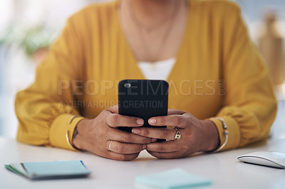 Buy stock photo Cropped shot of an unrecognizable businesswoman sitting alone in her office and using her cellphone