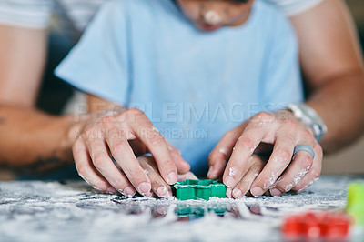 Buy stock photo Cropped shot of a little boy baking with his father at home