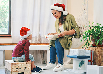 Buy stock photo Shot of a young woman reading a book with her adorable son at Christmas