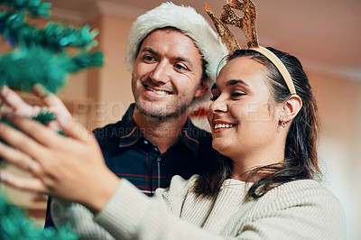 Buy stock photo Shot of a happy young couple decorating their Christmas tree together at home