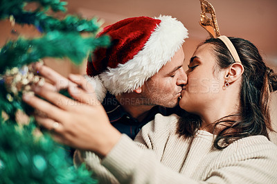 Buy stock photo Shot of an affectionate young couple decorating their Christmas tree together at home