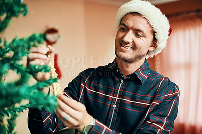 Buy stock photo Shot of a happy young man decorating his Christmas tree at home