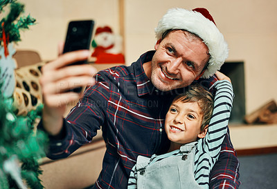 Buy stock photo Shot of an adorable little boy taking selfies with his father during Christmas at home