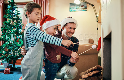 Buy stock photo Shot of two adorable little boys roasting marshmallows by the fireplace with their father at Christmas