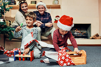 Buy stock photo Shot of two adorable little boys unwrapping Christmas presents with their parents at home