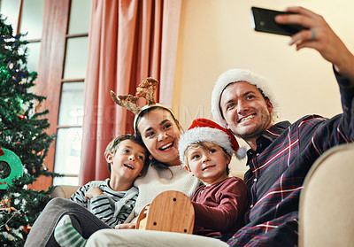 Buy stock photo Shot of a happy young family of four taking selfies during Christmas at home